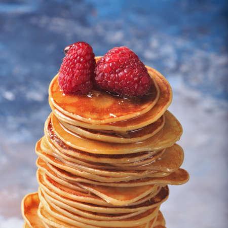 maslenitsa: Stack of pancakes with raspberries on top. Homemade dessert. Maslenitsa concept. Blue marble background. Square, macro