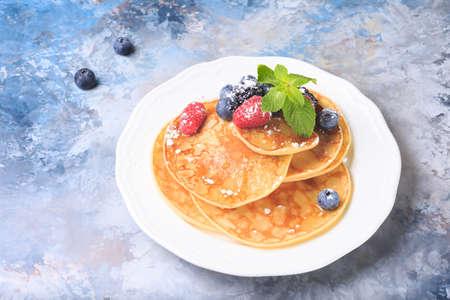 pancake week: Pancakes with berries and mint. Homemade dessert. Maslenitsa concept. Blue marble background. Horizontal Stock Photo