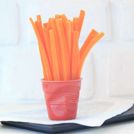 high key: Carrot slices in a red porcelain glass. Healthy snack. Fresh high key veggie photo. Black background with white napkin. Square