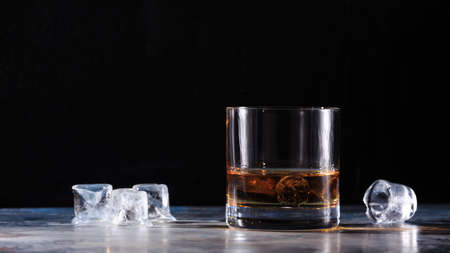 hard liquor: Glass of whiskey on the rocks  with some ice on the table. Concept of hard liquor. Horizontal, wide screen format