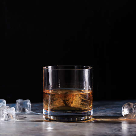 hard liquor: Glass of whiskey on the rocks  with some ice on the table. Concept of hard liquor. Square