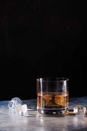 hard liquor: Glass of whiskey on the rocks with some ice on the table. Concept of hard liquor. Vertical