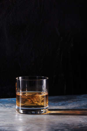 hard liquor: Glass of whiskey on the rocks on the table. Concept of hard liquor. Vertical Stock Photo