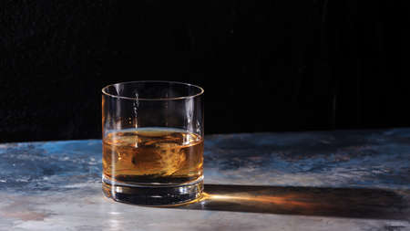 hard liquor: Glass of whiskey on the rocks on the table. Concept of hard liquor. Horizontal, wide screen format