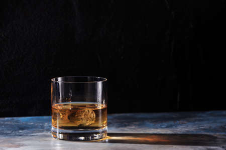 hard liquor: Glass of whiskey on the rocks on the table. Concept of hard liquor. Horizontal Stock Photo