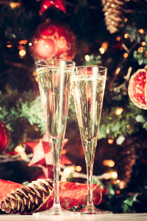 Two glasses of champagne with Christmas tree background. Holiday season background. Traditional red and green Christmas decoration with lights. Holiday party. Vertical