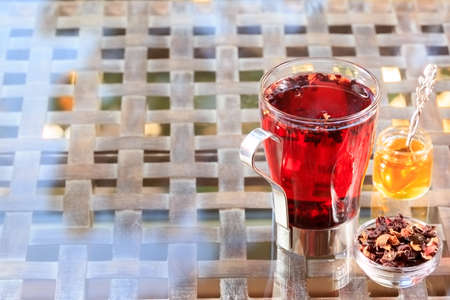 Concept of herbal tea. Hibiscus tea in a glass mug with honey. Healthy caffein-free drink. Neutral background. Horizontal