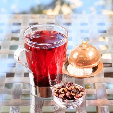 locum: Concept of herbal tea. Hibiscus tea in a glass mug with turkish locum. Healthy caffein-free drink. Neutral background. Square