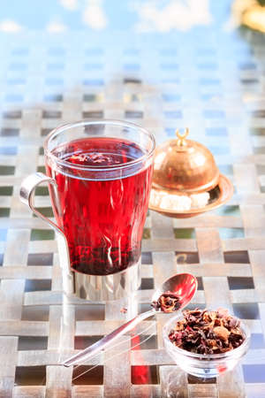 caffeine free: Concept of herbal tea. Hibiscus tea in a glass mug with turkish locum. Healthy caffein-free drink. Neutral background. Vertical Stock Photo