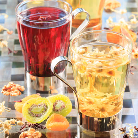caffeine free: Concept of herbal tea. Variety of herbal teas in glass mugs. Healthy caffein-free drinks with dried fruits. Chamomile, hibiscus and linden teas. Light airy caption. Grey background. Square
