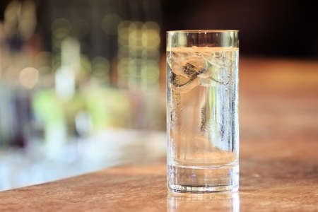 Glass of water with ice on the bar stand. Drink at the bar counter. Dark background. Horizontal
