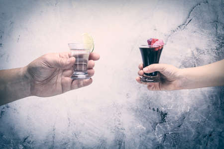 drink responsibly: Drink responsibly!  Adult hand with shot of tequila and kid hand with cola and jelly bears. Horizontal, grey toning