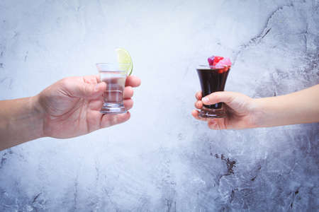 drink responsibly: Drink responsibly!  Adult hand with shot of tequila and kid hand with cola and jelly bears. Horizontal