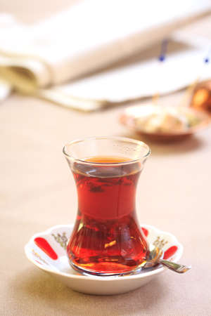 locum: Cup of turkish tea with locum on oriental plate. Concept of turkish tea. Beige tablecloth background. Vertical Stock Photo