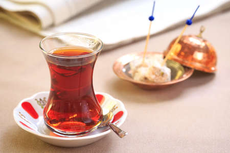 Cup of turkish tea with locum on oriental plate. Concept of turkish tea. Beige tablecloth background. Horizontal Imagens - 64900936