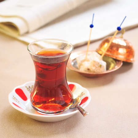 locum: Cup of turkish tea with locum on oriental plate. Concept of turkish tea. Beige tablecloth background. Square