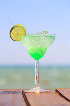 Green fairy cocktail on the wooden pier. Concept of exotic cocktail. Seaside vacation. Vertical, zero level view