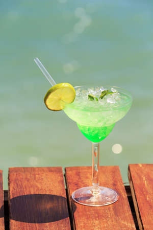 Green fairy cocktail on the wooden pier. Concept of exotic cocktail. Seaside vacation. Vertical, focus on lemon