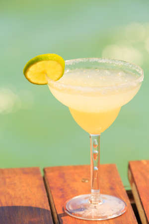 Margarita cocktail on the wooden pier. Concept of classic drink. Vacation background. Vertical. Shallow DOF