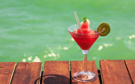 Frozen Strawberry Daiquiri cocktail on the wooden pier. Concept of classic cocktail. Vacation background. Horizontal, wide screen format. Shallow DOF