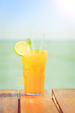 Mango mojito on the wooden pier with blue sky. Concept of luxury tropical vacation. Classic cocktail. Toned, vertical, sun glare