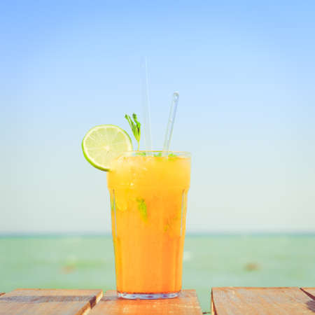 Mango mojito on the wooden pier with blue sky. Concept of luxury tropical vacation. Classic cocktail. Toned, square Stock Photo