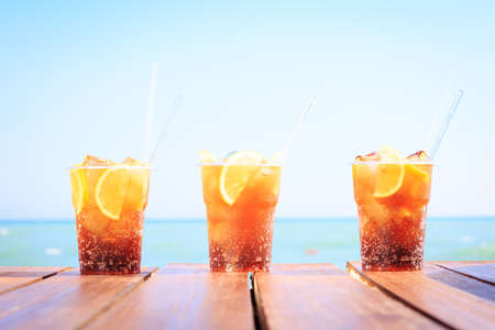 Concept of luxury vacation. Cuba Libre cocktail on the pier. Long island ice tea cocktail on the pier. Tropical vacation background. Beach party. Clear blue sky. Horizontal