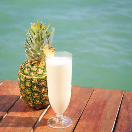 upscale: Pina colada cocktail with pine apple at the sea pier. Concept of luxury vacation. Beach party. Upscale resort background. Square