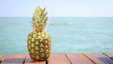 Exotic cocktail in the pineapple. Sea pier. Concept of luxury vacation. Beach party. Upscale resort background. Blue sky at the background. Horizontal, wide screen format Stock Photo