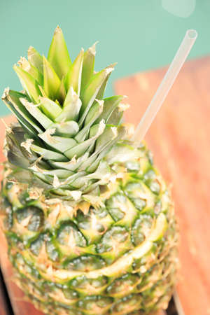 Exotic cocktail in the pineapple. Sea pier. Concept of luxury vacation. Beach party. Upscale resort background. Top view. Vertical, close up, macro view Stock Photo