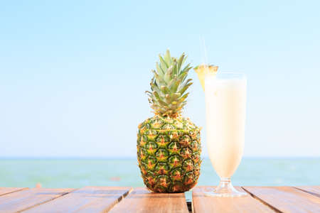 colada: Pina colada cocktail with pine apple at the sea pier. Concept of luxury vacation. Beach party. Upscale resort background. Blue sky at the background. Horizontal Stock Photo