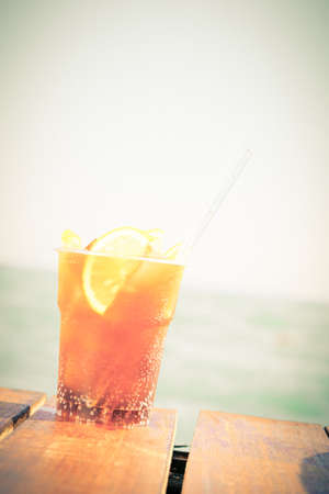 Concept of luxury vacation. Cuba Libre cocktail on the pier. Long island ice tea cocktail on the pier. Tropical vacation background. Right side angle. Clear blue sky. Vertical, toned