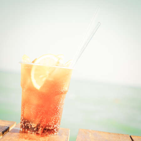 Concept of luxury vacation. Cuba Libre cocktail on the pier. Long island ice tea cocktail on the pier. Tropical vacation background. Right side angle. Clear blue sky. Square, toned