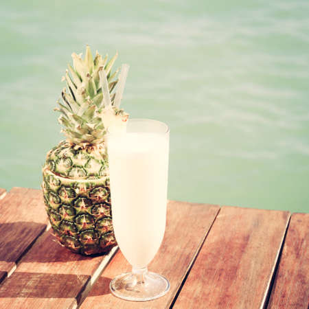 colada: Pina colada cocktail with pine apple at the sea pier. Concept of luxury vacation. Beach party. Upscale resort background. Square