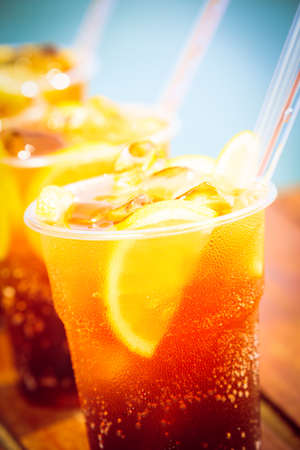 Concept of luxury vacation. Cuba Libre cocktail on the pier. Long island ice tea cocktail on the pier. Tropical vacation background. Beach party. Macro. Left side angle. Vertical