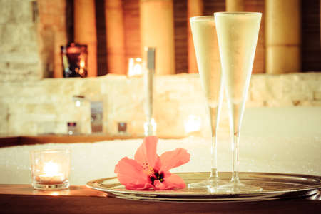 swimming candles: Two glasses of champagne with candle and red flower near jacuzzi. Valentines background. Romance concept. Horizontal, toned Stock Photo