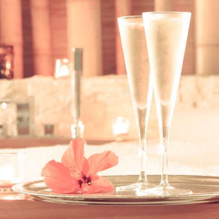 swimming candles: Two glasses of champagne with candle and red flower near jacuzzi. Valentines background. Romance concept. Square, toned Stock Photo