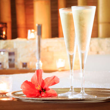 swimming candles: Two glasses of champagne with candle and red flower near jacuzzi. Valentines background. Romance concept. Square