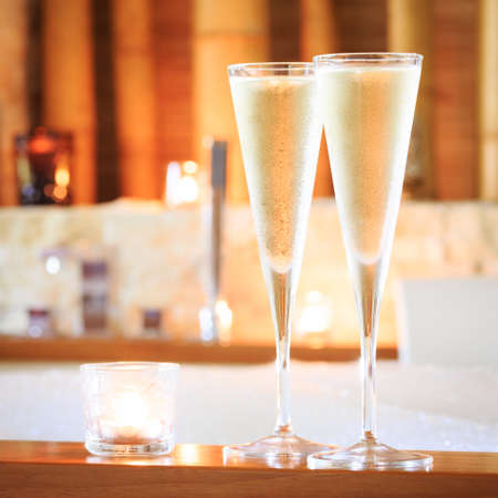 swimming candles: Two glasses of champagne with candle near jacuzzi. Valentines background. Romance concept. Square