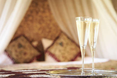Two champagne glasses with oriental canopy bed at the background. Silver tray. Romantic concept. Valentines background. Arabian nights ambiance. Horizontal, glasses on right side Stock Photo