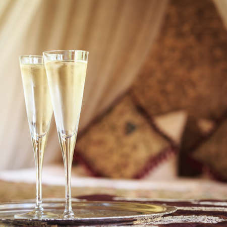 Two champagne glasses with oriental canopy bed at the background. Silver tray. Romantic concept. Valentines background. Arabian nights ambiance. Square, front view, glasses on left side, blur background
