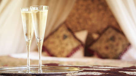 Two champagne glasses with oriental canopy bed at the background. Silver tray. Romantic concept. Valentines background. Arabian nights ambiance. Horizontal, wide screen, glasses on left side Stock Photo