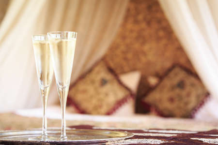 Two champagne glasses with oriental canopy bed at the background. Silver tray. Romantic concept. Valentines background. Arabian nights ambiance. Horizontal