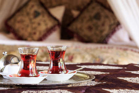 Two turkish tea cups and turkish delight with oriental canopy bed at the background. Silver tray. Romantic concept. Valentines background. Arabian nights ambiance. Horizontal, cups on the left side Imagens