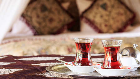 Two turkish tea cups and turkish delight with oriental canopy bed at the background. Silver tray. Romantic concept. Valentines background. Arabian nights ambiance. Horizontal, wide screen, cups on the right side Stock Photo