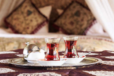 Two turkish tea cups and turkish delight with oriental canopy bed at the background. Silver tray. Romantic concept. Valentines background. Arabian nights ambiance. Horizontal, cups in the middle 写真素材