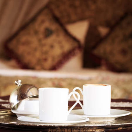 Two turkish coffee cups and turkish delight with oriental canopy bed at the background. Silver tray. Romantic concept. Valentines background. Arabian nights ambiance. Square, semi-defined background