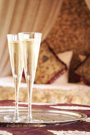 Two champagne glasses with oriental canopy bed at the background. Silver tray. Romantic concept. Valentines background. Arabian nights ambiance. Vertical