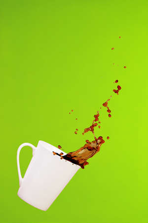 Coffee concept. Minimal art. Solid background. Coffee splashes. Levitating mug. Greenery background. Vertical, diagonal cup
