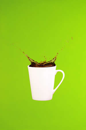 Coffee concept. Minimal art. Solid background. Coffee splashes. Levitating mug. Greenery background. Vertical, straight cup